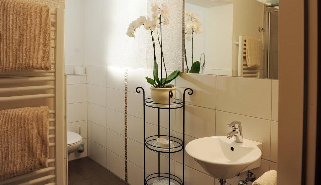 Mit Orchideen dekoriertes Badezimmer in der Pension am Rain in Winden im Elztal