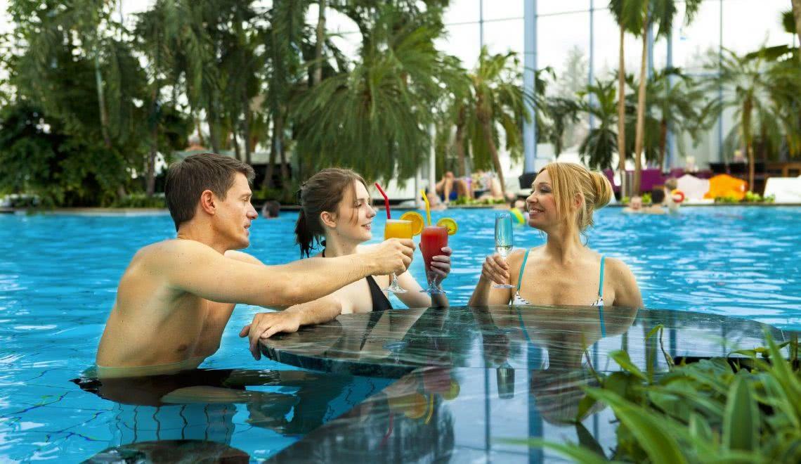 Freunde mit Cocktails an der Poolbar in der Palmenoase im Badeparadies Galaxy in Titiesee im Schwarzwald