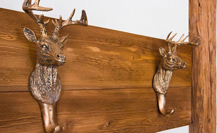 Bronzefarbene Hirschkopf-Garderobe an edlem Nussbaumholz in Apartment der Pension am Rain