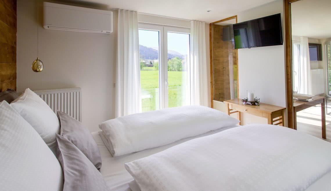 Schlafzimmer mmit Wiesenblick im Apartment Nussbaumin Holzoptik in der Pension am Rain