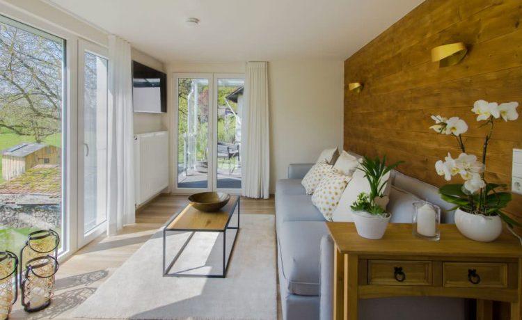 Wonzimmer des Apartments mit Nussbaum-Holzwand und Wiesen Ausblick